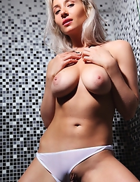 """""""Isabella D poses in the bathroom, her curvy physique and magnificent breasts standing out against the tiled wall."""""""